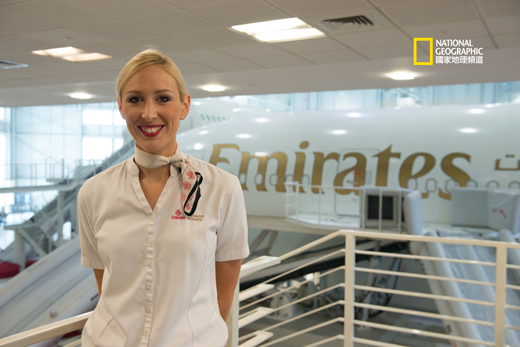 Dubai Internatioanl Airport - Fiona Devlin, Cabin Crew Trainer, with Emirates training simulator in the background.